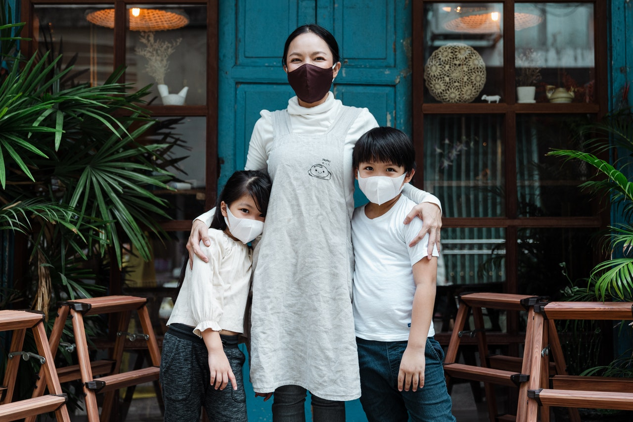 Cheerful mother with children wearing masks
